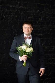 Pan młody w garniturze trzyma bukiet ślubny