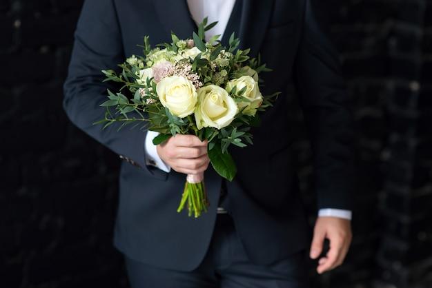 Pan młody w garniturze trzyma zbliżenie bukiet ślubny