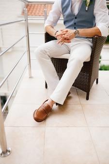 Pan młody w kamizelce z butonierką siedzi w plecionym krześle na balkonie