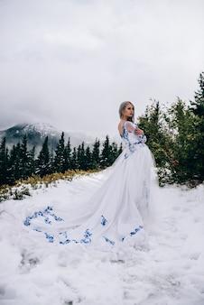 Pan młody w niebieskim garniturze i panna młoda w białym, haftowanym niebieskim wzorem