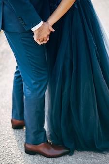 Pan młody w niebieskim garniturze trzyma rękę panny młodej w niebieskiej sukience z bliska widok z dołu