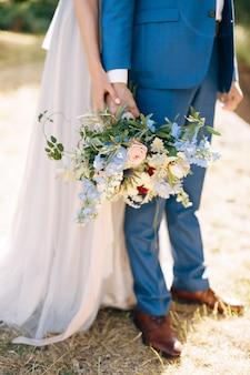 Pan młody w niebieskim garniturze trzyma w dłoni bukiet kwiatów panna młoda w białej sukni przytula go