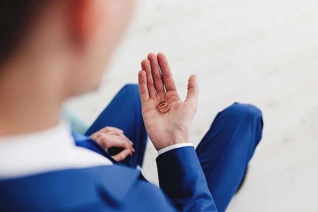 Pan młody w niebieskim garniturze trzyma w ręku obrączki.