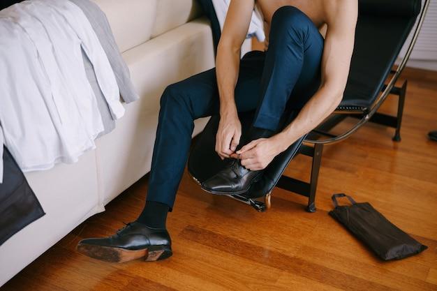 Pan młody w spodniach siada na krześle i sznuruje buty