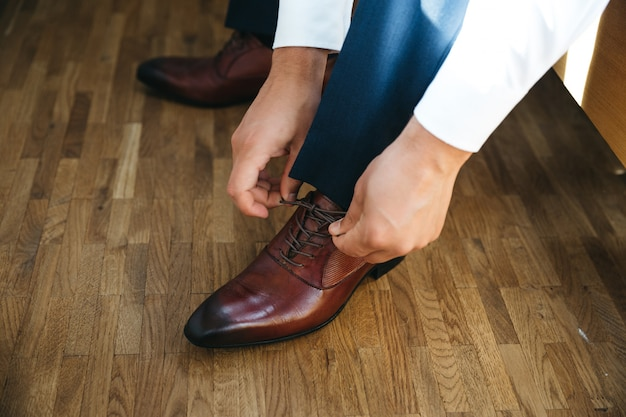Pan młody wiąże koronki na swoich butach