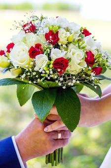 Pan młody wręcza ukochanemu wykwintny bukiet ślubny. manifestacja miłości, romantyczny związek