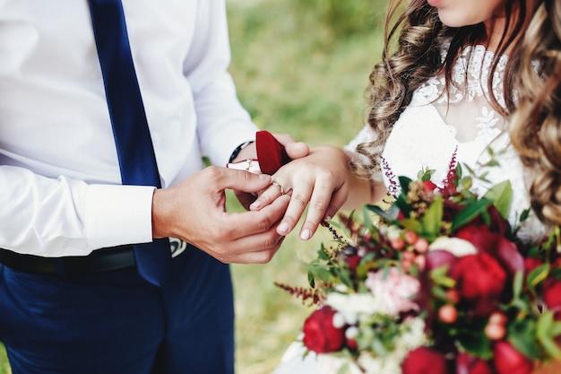 Pan młody zakłada obrączkę na palec panny młodej. bukiet ślubny.