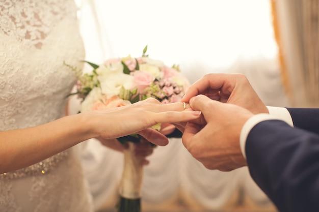 Pan młody zakłada pierścień na rękę panny młodej.