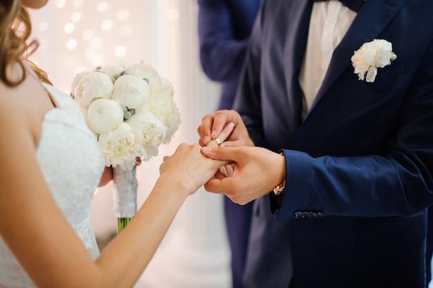 Pan młody zakłada złotą obrączkę na palec panny młodej w białej sukni