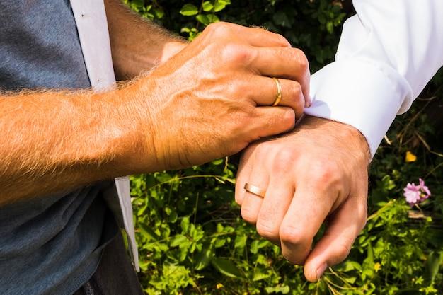 Pan młody zakładający spinki do mankietów, gdy ubiera się w dniu ślubu. garnitur pana młodego