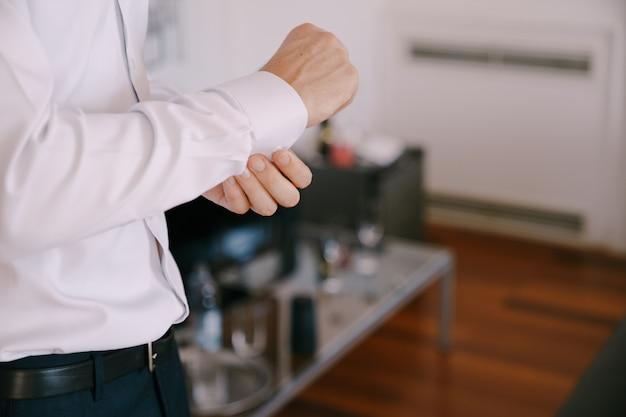 Pan młody zapina guziki na mankiecie białej koszuli