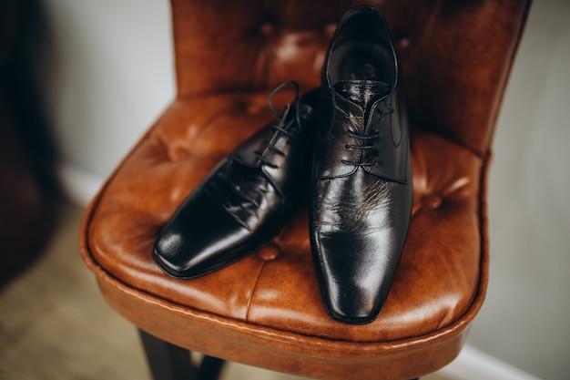 Pan młody zbiera się rano. szare krzesło. męskie czarne klasyczne lakierowane buty. czarna muszka. szczegóły ślubu.