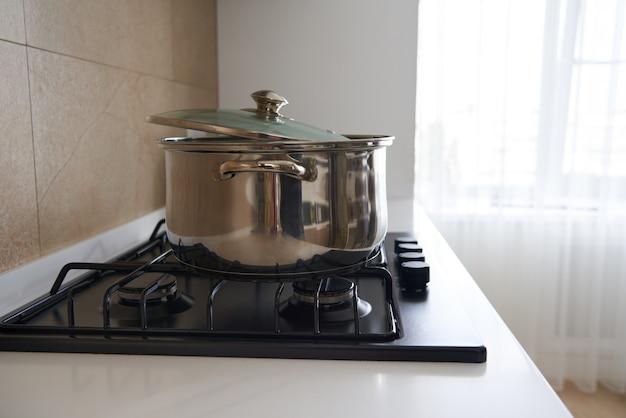 Pan na kuchence gazowej we wnętrzu kuchni koncepcja naczyń do gotowania garnków ze stali nierdzewnej