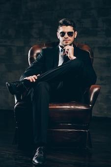 Pan perfection.young przystojny mężczyzna w garniturze i okularach przeciwsłonecznych, trzymając rękę na brodzie i patrząc na kamerę siedząc w skórzanym fotelu na ciemnoszarym tle