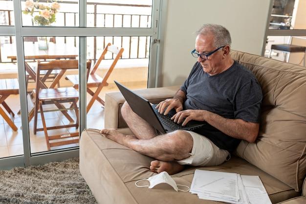 Pan pisze na notebooku, pracuje w domu w systemie biura domowego w czasach pandemii wirusa covid-19. lord pracuje w domu w lekkim ubraniu iz maską leżącą obok.