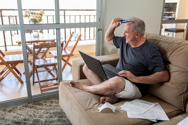 Pan pisze na notebooku, pracuje w domu w systemie home office w czasach pandemii koronawirusa. pan pracuje w domu w lekkim ubraniu, a obok niego leży maska.