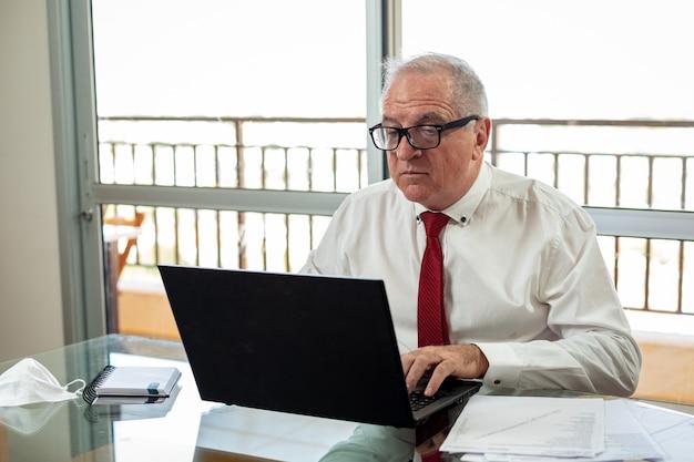 Pan pisze na notebooku, pracuje w systemie domowego biura. pan pracuje w domu, ubrany w koszulę i krawat, a obok niego leży maska.