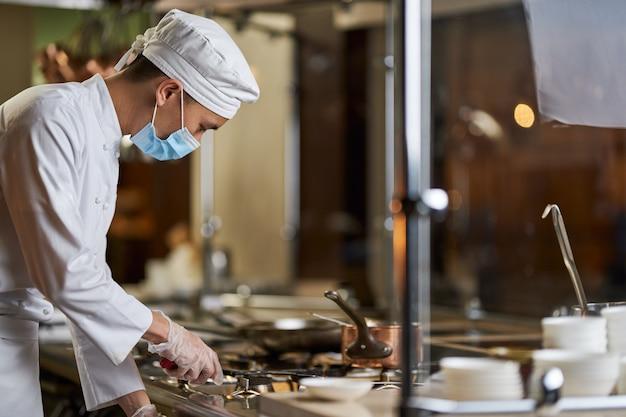 Pan w mundurze szefa kuchni włączający kuchenkę gazową