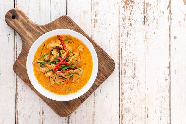 Panang moo, panaeng mu, tajskie jedzenie, czerwone curry z wieprzowiną, mlekiem kokosowym, liśćmi bergamotki, liśćmi bazylii i chili na desce do krojenia na starym białym tle tekstury drewna z kopią miejsca na tekst, widok z góry