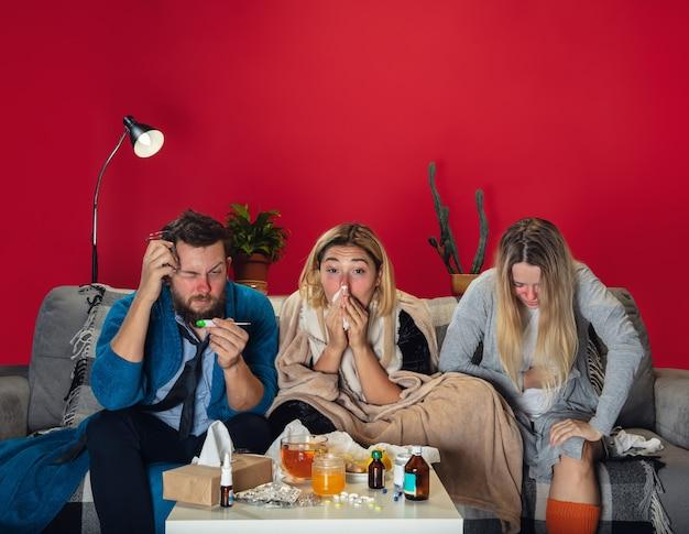 Pandemia. chorzy młodzi ludzie z gorączką i zimnem patrzą na cierpienie. czuję się chory, siny, wciągający nosem. zimno, wirus, grypa sezonowa. mężczyzna i kobieta siedzi na kanapie z miodem, herbatą, tabletkami w domu razem.