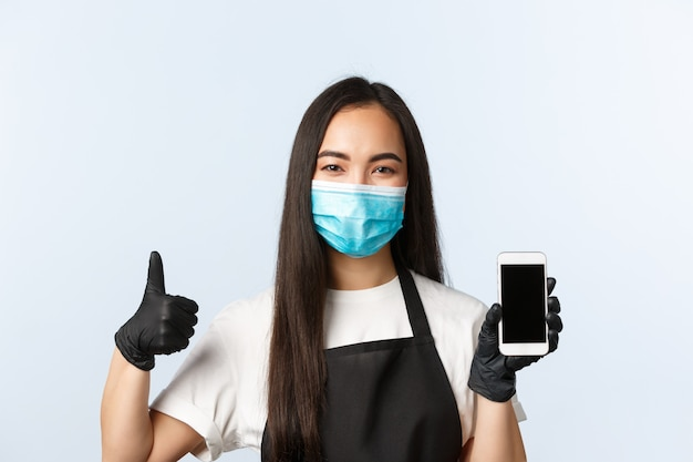 Pandemia covid-19, kawiarnia, mała firma i koncepcja zapobiegania wirusowi. uśmiechnięty atrakcyjny właściciel azjatyckiej kawiarni, barista pokazujący ekran smartfona i kciuk w górę, nosić maskę medyczną