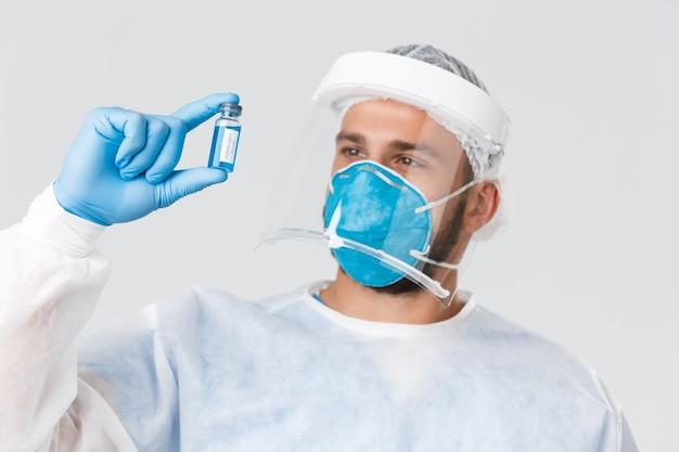 Pandemia covid-19, wybuch wirusa, koncepcja pracowników kliniki i opieki zdrowotnej. zadowolony lekarz, badacz laboratorium klinicznego w zakresie środków ochrony osobistej, patrzący na szczepionkę na koronawirusa.