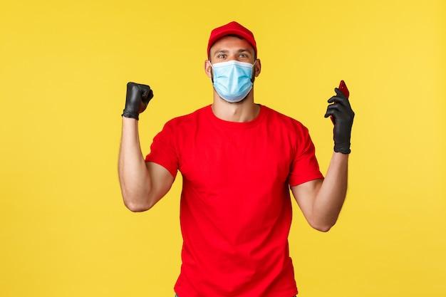 Pandemia ekspresowych dostaw, covid-19, bezpieczna wysyłka, koncepcja zakupów online. zadowolony podekscytowany kurier w czerwonym mundurze, masce medycznej i rękawiczkach, śpiewający, świętujący dobre wieści, trzymający telefon komórkowy
