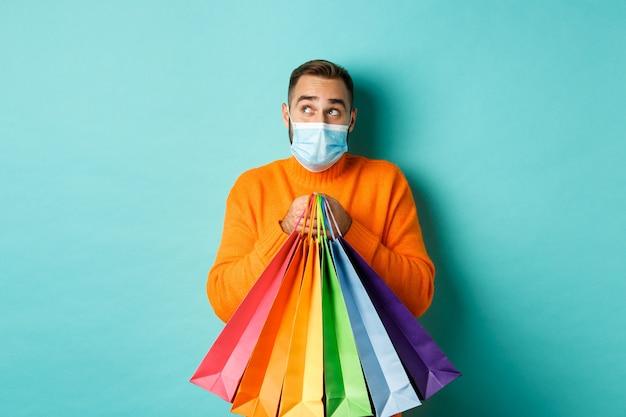 Pandemia i styl życia. człowiek myśli, nosząc maskę, trzymając torby na zakupy