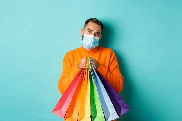 Pandemia i styl życia. niezadowolony i niechętny mężczyzna w masce medycznej, trzymając