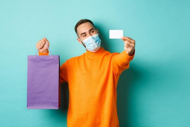 Pandemia i styl życia. szczęśliwy klient męski w masce pokazano kartę kredytową