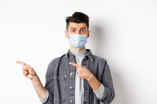 Pandemia koncepcja stylu życia, opieki zdrowotnej i medycyny. młody facet w masce na twarz, zapraszający, patrzy tutaj, wskazując palcem w lewo na logo, stojąc na białym tle.