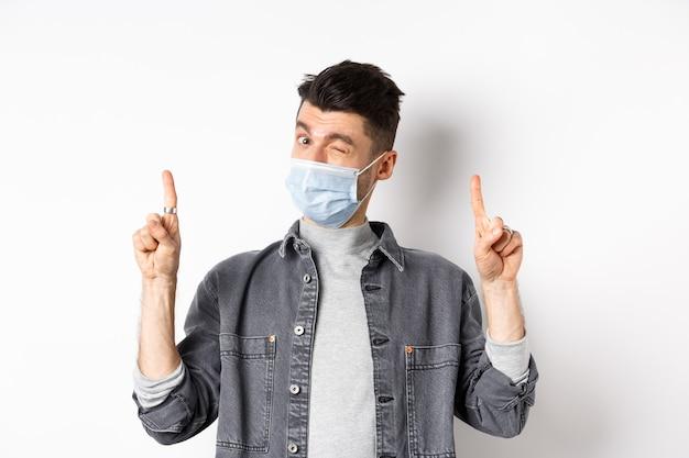 Pandemia koncepcja stylu życia, opieki zdrowotnej i medycyny. przystojny młody mężczyzna mruga w masce medycznej, ogłasza, pokazuje ofertę promocyjną, wskazuje palcami w górę, białe tło.