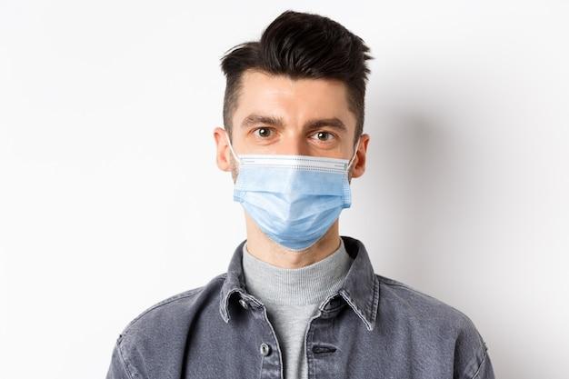 Pandemia koncepcja stylu życia, opieki zdrowotnej i medycyny. zamknij się szczery młody człowiek ubrany w maskę medyczną z covid-19, dbając o zdrowie, stojąc na białym tle.