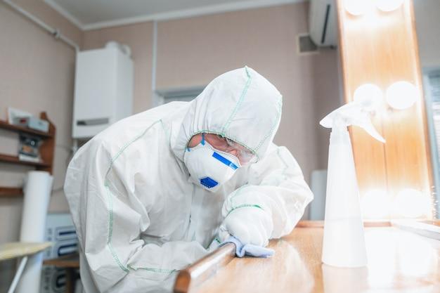 Pandemia koronawirusa dezynfektor w kombinezonie ochronnym i masce rozpyla środki dezynfekujące
