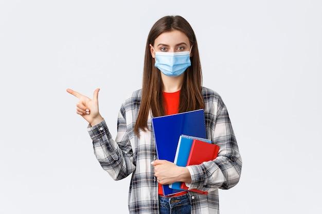 Pandemia koronawirusa, edukacja covid-19 i koncepcja powrotu do szkoły. młoda ładna studentka w masce medycznej z notebookami, wskazując palcem w lewo, pokazując informacje o uniwersytecie.