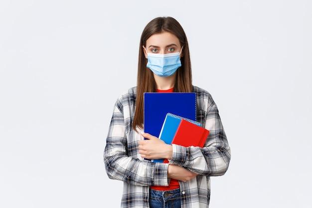 Pandemia koronawirusa, edukacja covid-19 i koncepcja powrotu do szkoły. młoda studentka w masce medycznej trzymająca zeszyty, idąca na zajęcia, studentka pierwszego roku na uniwersytecie w osobistej masce ochronnej
