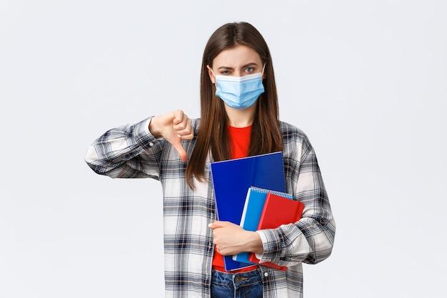 Pandemia koronawirusa, edukacja covid-19 i koncepcja powrotu do szkoły. niezadowolona i rozczarowana studentka, studentka pierwszego roku w masce medycznej z kciukiem w dół i krzywiąc się, omawiając coś złego