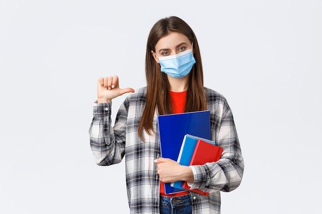 Pandemia koronawirusa, edukacja covid-19 i koncepcja powrotu do szkoły. pewna siebie, bezczelna studentka wskazująca się, nosząca maskę medyczną, studiująca na uniwersytecie, trzymająca zeszyty.