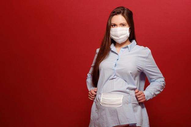 Pandemia koronawirusa, młoda kobieta w ciąży na czerwono w ochronnej masce medycznej trzyma się na brzuchu