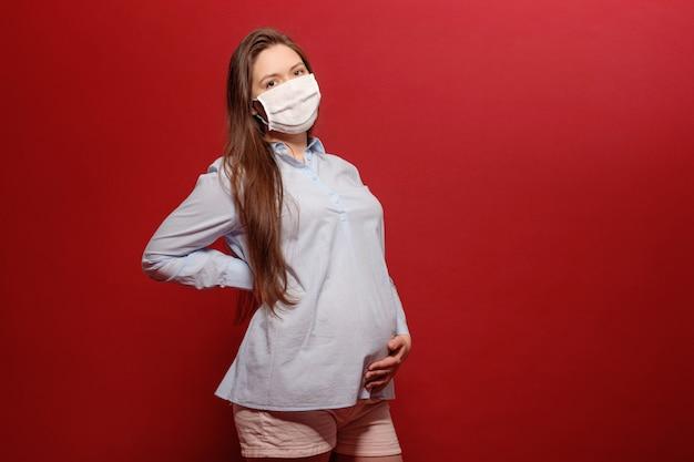 Pandemia koronawirusa, młoda kobieta w ciąży na czerwonym tle w ochronnej masce medycznej trzyma się na brzuchu