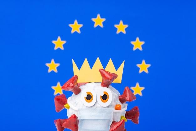 Pandemia koronawirusa w europie. ręcznie wykonany model celi covid-19 z koroną, ubrany w maskę medyczną przed flagą unii europejskiej.