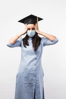 Pandemia korony i zamieszanie wokół egzaminów uniwersyteckich w indiach - ładna indyjska studentka ze zdezorientowanymi wyrazami twarzy, ubrana w medyczną maskę i kapelusz dyplomowy