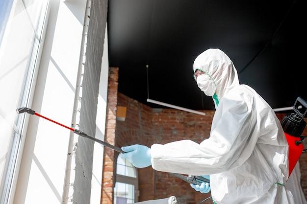 Pandemia wirusa koronawirusa. środek dezynfekujący w kombinezonie ochronnym i masce rozpyla środki dezynfekujące w pomieszczeniu.