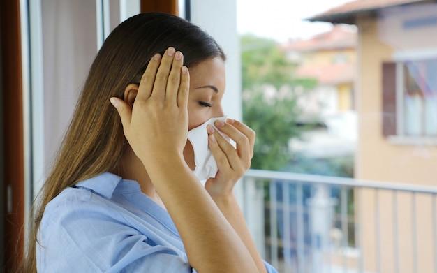 Pandemiczna maska koronawirusa covid-19 chora kobieta kichanie, kaszel wydmuchiwanie nosa