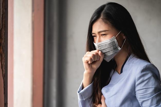 Pandemiczny koronawirus covid-19, azjatka ma przeziębienie i objawy kaszlu, gorączki, bólu głowy i bólów