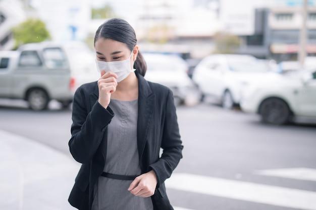 Pandemiczny koronawirus covid-19 azjatka na ulicy miejskiej nosząca maskę ochronną na wypadek rozprzestrzeniania się wirusa choroby sars-cov-2. dziewczyna z maską ochronną na twarzy przed chorobą koronawirusa 2019.