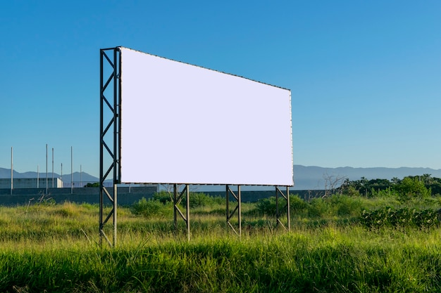 Panel reklamowy na terenie porośniętym roślinnością