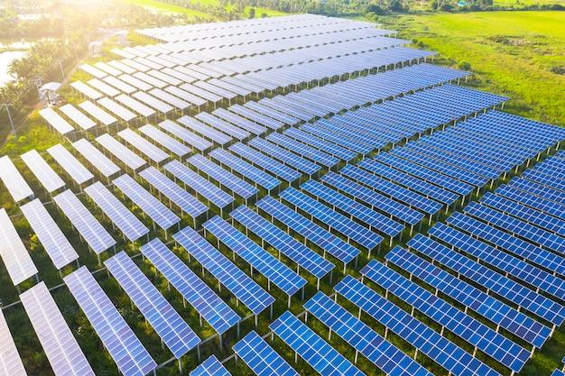 Panel słoneczny na pięknym pomarańczowym zmierzchu tle. zielona trawa i pochmurne niebo. koncepcja energii alternatywnej