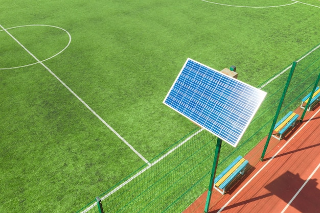 Panel słoneczny na stojaku. panel znajduje się na boisku sportowym. oświetlenie stadionu.