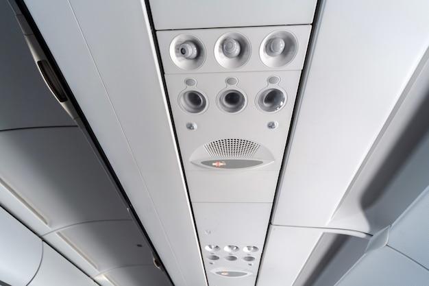 Panel sterowania klimatyzacją samolotu nad siedzeniami. zatkane powietrze w kabinie samolotu z ludźmi. nowa tania linia lotnicza